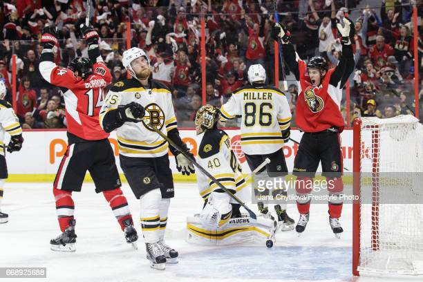 Kyle Turris and Alexandre Burrows of the Ottawa Senators celebrate the overtime goal scored by team mate Dion Phaneuf as Joe Morrow Tuukka Rask and...