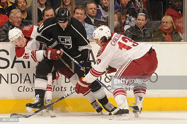 Kyle Turris and Daniel Carcillo of the Phoenix Coyotes battle for the puck against Raitis Ivanans of the Los Angeles Kings during the game on...
