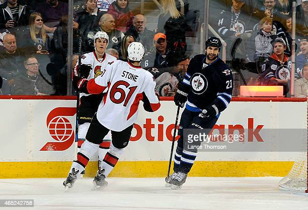 Kyle Turris and Mark Stone of the Ottawa Senators celebrate a first period goal as Jay Harrison of the Winnipeg Jets skates away on March 4 2015 at...