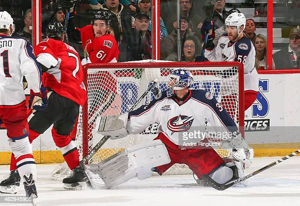 Kyle Turris of the Ottawa Senators hits the post as the puck ricochets behind Curtis McElhinney of the Columbus Blue Jackets with Mark Stone and...
