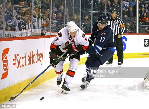 Kyle Turris of the Ottawa Senators plays the puck along the boards as Adam Lowry of the Winnipeg Jets gives chase during third period action at the...