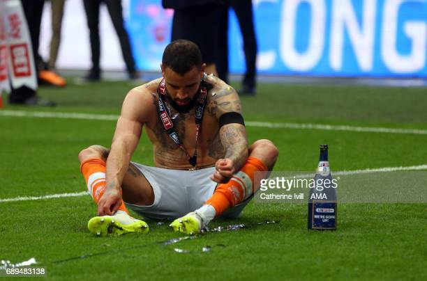 Kyle Vassell of Blackpool sits on the pitch next to a bottle of champagne during the Sky Bet League Two Playoff Final match between Blackpool and...