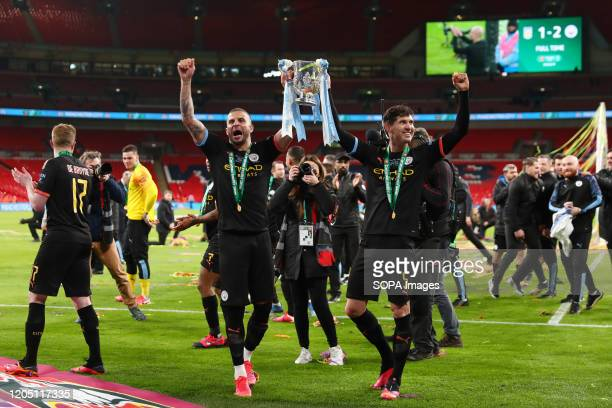 Kyle Walker and John Stones of Manchester City are seen celebrating with the trophy after the Carabao Cup Final match between Aston Villa and...