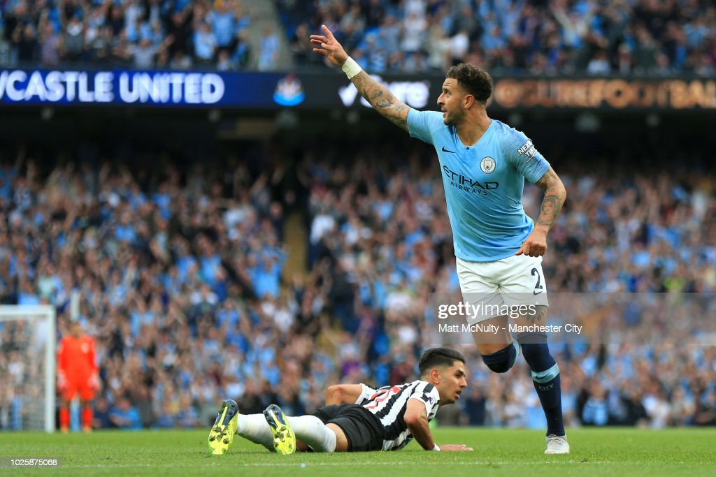 Kyle Walker of Manchester City celebrates after scoring his team's second goal as Ayoze Perez of Newcastle United reacts during the Premier League match between Manchester City and Newcastle United at Etihad Stadium on September 1, 2018 in Manchester, United Kingdom.