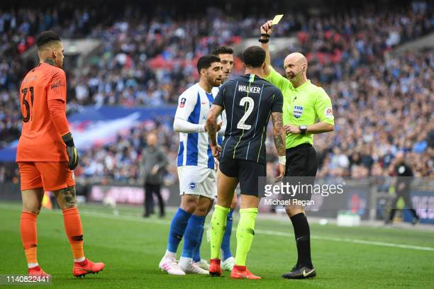 Kyle Walker of Manchester City is shown a yellow card by referee Anthony Taylor after clashing with Alireza Jahanbakhsh of Brighton and Hove Albion...