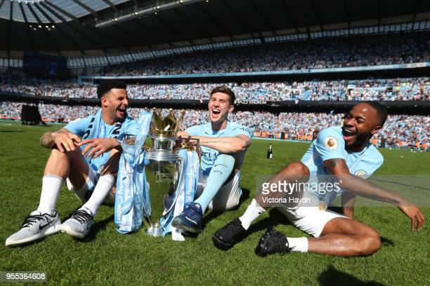 Kyle Walker of Manchester City John Stones of Manchester City and Raheem Sterling of Manchester City celebrates with The Premier League Trophy after...