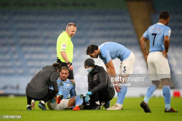 Kyle Walker of Manchester City receives medical treatment as team mate Ruben Dias watches over during the Premier League match between Manchester...