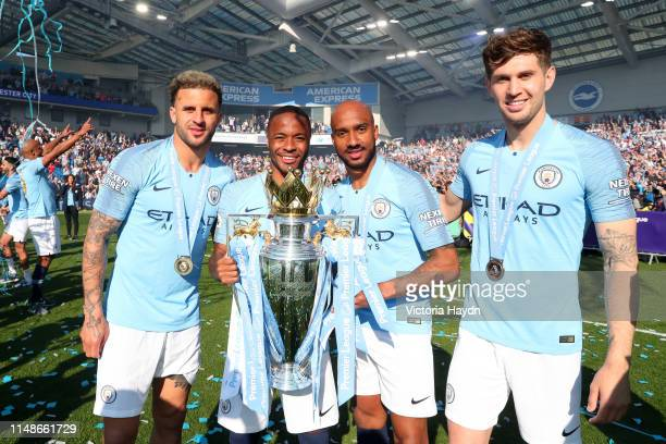 Kyle Walker, Raheem Sterling, Fabian Delph and John Stones of Manchester City pose with the Premier League Trophy after winning the title following...