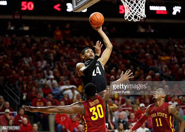 Kyle Washington of the Cincinnati Bearcats takes a shot over Deonte Burton and Monte Morris of the Iowa State Cyclones in the second half of play at...