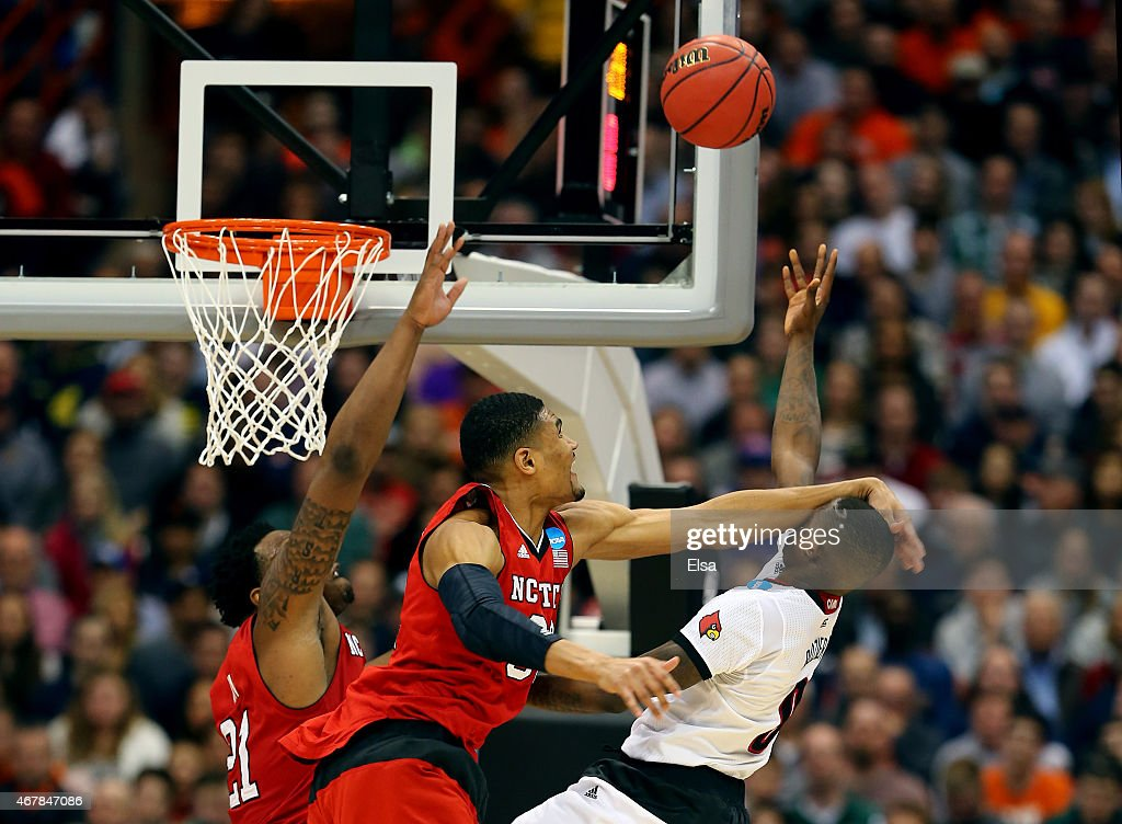 Kyle Washington #32 of the North Carolina State Wolfpack fouls Terry Rozier #0 of the Louisville Cardinals in the second half of the game during the East Regional Semifinal of the 2015 NCAA Men's Basketball Tournament at the Carrier Dome on March 27, 2015 in Syracuse, New York.