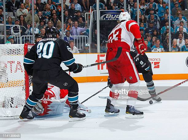 Kyle Wellwood and Joe Pavelski of the San Jose Sharks surround the net against Brad Stuart and Jimmy Howard of the Detroit Red Wings in Game Seven of...