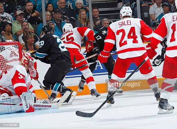 Kyle Wellwood and Torrey Mitchell of the San Jose Sharks battle for the puck against Ruslan Salei, Niklas Kronwall, and Jimmy Howard of the Detroit...