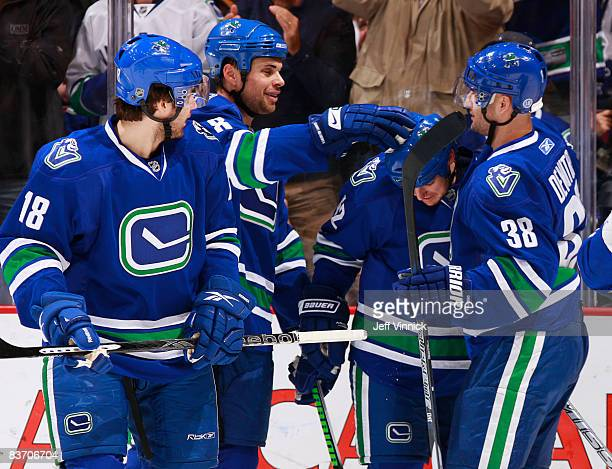 Kyle Wellwood of the Vancouver Canucks gets congratulated by his teammates Willie Mitchell Pavol Demitra and Steve Bernier after scoring a goal...