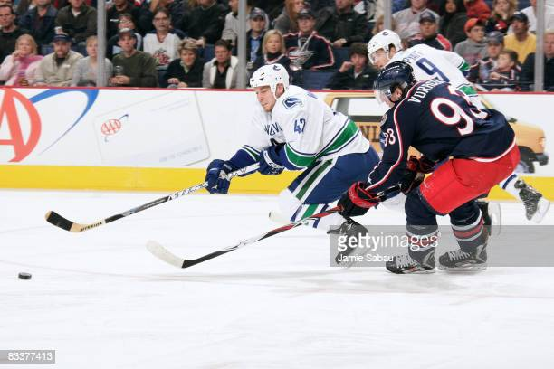 Kyle Wellwood of the Vancouver Canucks is tripped up by Jakub Voracek of the Columbus Blue Jackets on October 21 2008 at Nationwide Arena in Columbus...