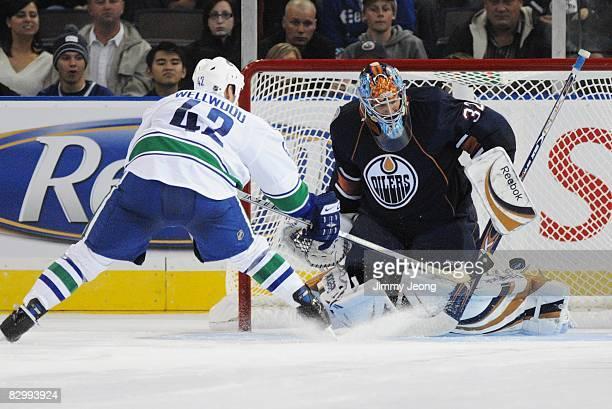 Kyle Wellwood of the Vancouver Canucks scores a shootout goal past goaltender Mathieu Garon of the Edmonton Oilers during an NHL preseason game on...