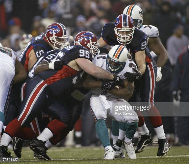 Kyle Williams and Aaron Schobel of the Buffalo Bills tackle Sammy Morris of the Miami Dolphins on December 17 2006 at Ralph Wilson Stadium in Orchard...
