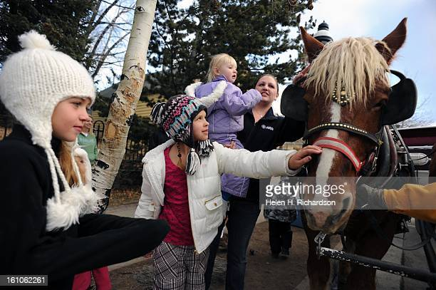 Kylee Winner left and Alyssa Linson 8, seem delighted to gently pat Spike, a Belgian draft horse, on the nose in downtown Breckenride. Also petting...