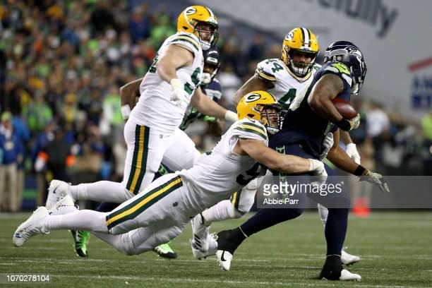 Kyler Fackrell of the Green Bay Packers tackles Rashaad Penny of the Seattle Seahawks in the third quarter during their game at CenturyLink Field on...