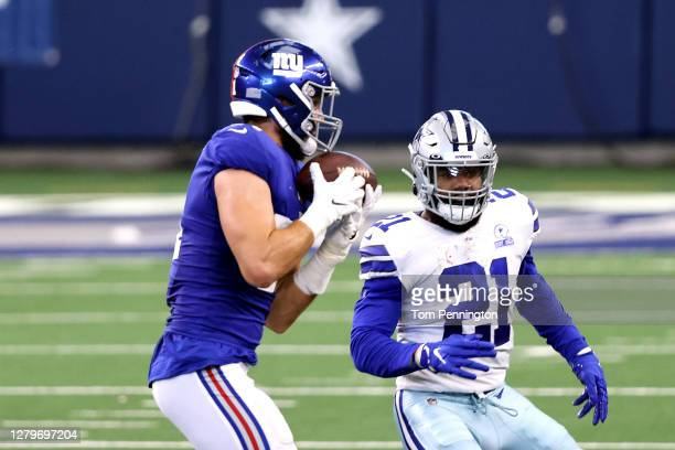 Kyler Fackrell of the New York Giants intercepts the ball and returns it past Ezekiel Elliott of the Dallas Cowboys for a touchdown during the first...