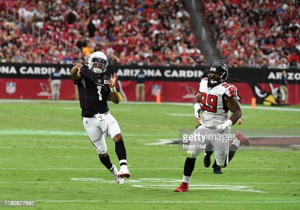 Kyler Murray of the Arizona Cardinals throws the ball down field while being chased by Adrian Clayborn of the Atlanta Falcons at State Farm Stadium...