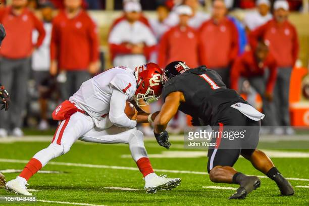 Kyler Murray of the Oklahoma Sooners is hit and brought down by Jordyn Brooks of the Texas Tech Red Raiders during the first half of the game on...
