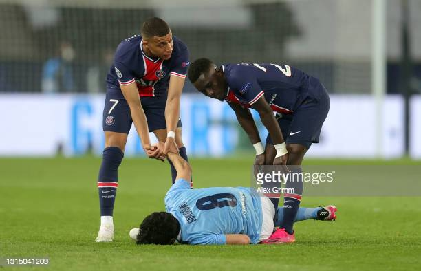 Kylian Mbappe and Idrissa Gueye of Paris Saint-Germain check on Ilkay Gundogan of Manchester City after a challenge by Idrissa Gueye leading to him...
