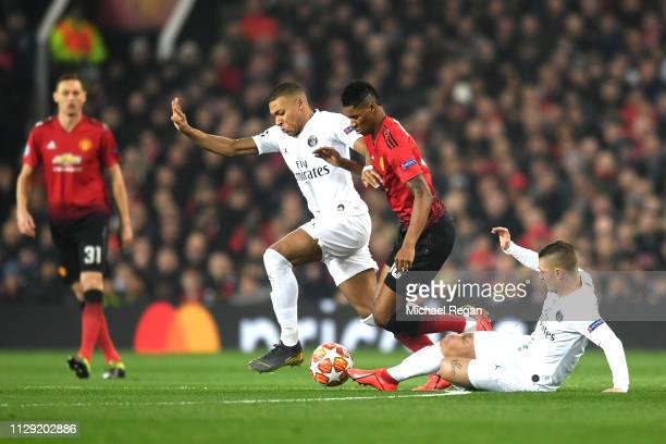 Kylian Mbappe and Marco Verratti tackle Marcus Rashford of Manchester United during the UEFA Champions League Round of 16 First Leg match between...
