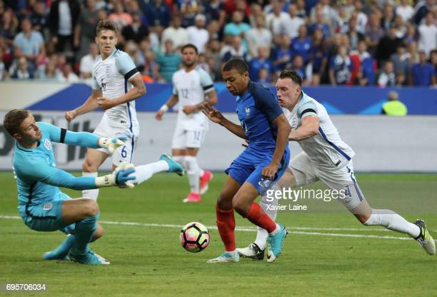 Kylian Mbappe in action over Tom Heaton of England during the International Friendly match between France and England at Stade de France on June 13...