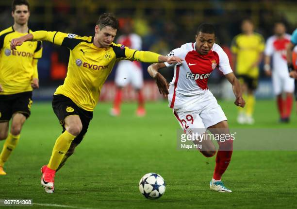 Kylian Mbappe of AS Monaco holds off pressure from Lukasz Piszczek of Borussia Dortmund during the UEFA Champions League Quarter Final first leg...