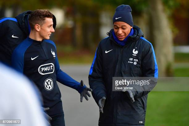 Kylian Mbappe of France and Lucas Digne of France share a joke as they arrive for the training session at the Centre National de Football in...