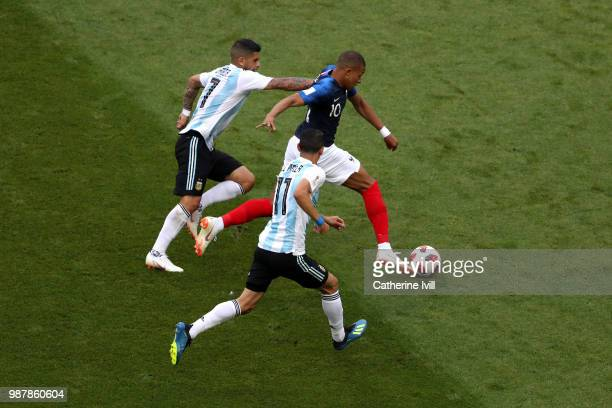 Kylian Mbappe of France challenge for the ball with Ever Banega and Angel Di Maria of Argentina during the 2018 FIFA World Cup Russia Round of 16...