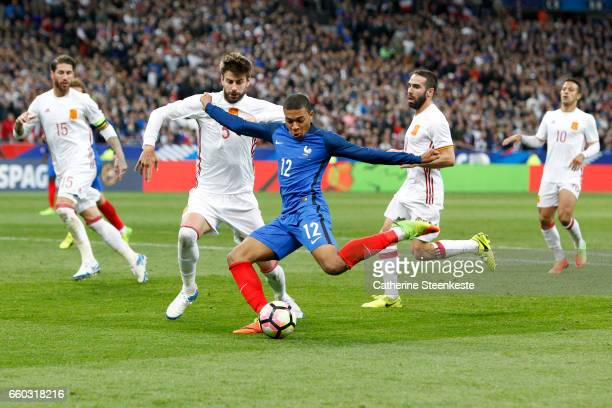 Kylian MBappe of France controls the ball against Gerard Pique of Spain during the International Friendly game between France and Spain at Stade de...