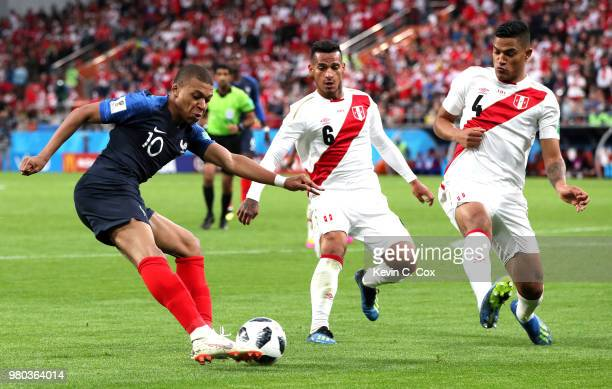 Kylian Mbappe of France crosses the ball under pressure from Miguel Trauco of Peru and Anderson Santamaria of Peru during the 2018 FIFA World Cup...