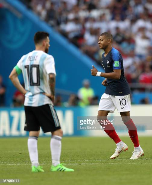 Kylian Mbappe of France gives a thumbs up in celebration as walking past Lionel Messi of Argentina during the 2018 FIFA World Cup Russia Round of 16...