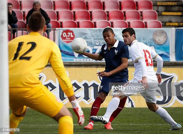 Kylian Mbappe of France in action against Milos Zlatkovic and goalkeeper Vanja MilinkovicSavic of Serbia during the UEFA European U19 Championship...