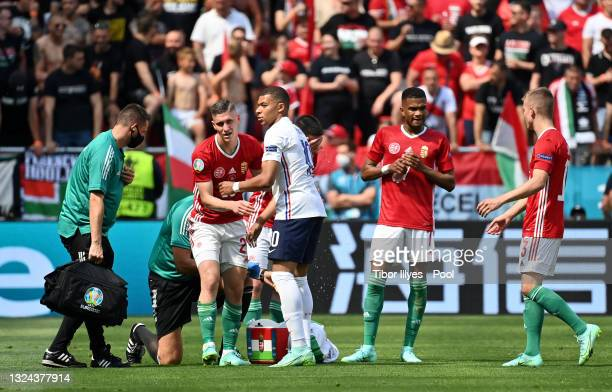 Kylian Mbappe of France interacts with Roland Sallai of Hungary after receiving medical treatment during the UEFA Euro 2020 Championship Group F...
