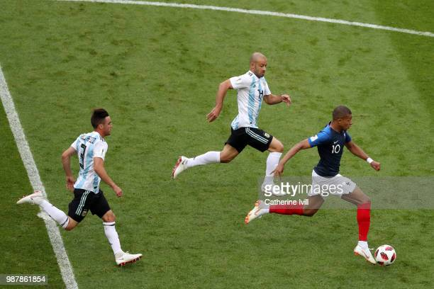 Kylian Mbappe of France is chased by Javier Mascherano anf Nicolas Tagliafico of Argentina during the 2018 FIFA World Cup Russia Round of 16 match...