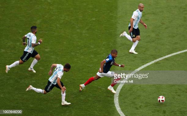 Kylian Mbappe of France is chased by Javier MascheranoNicolas Tagliafico and Ever Banega of Argentina during the 2018 FIFA World Cup Russia Round of...