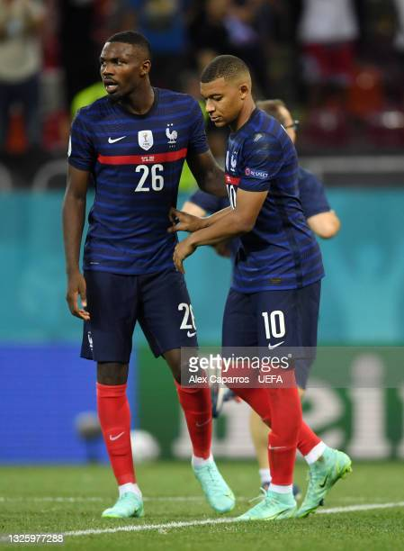 Kylian Mbappe of France is consoled by team mate Marcus Thuram as he looks dejected after having their side's decisive penalty saved by Yann Sommer...