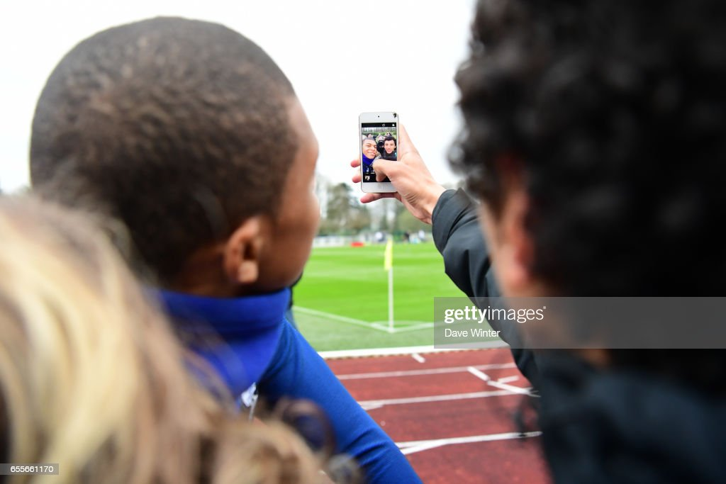 Kylian Mbappe of France poses for a selfie with a fan during the trainig session of the soccer french national team at Centre National du Football on March 20, 2017 in Clairefontaine, France.