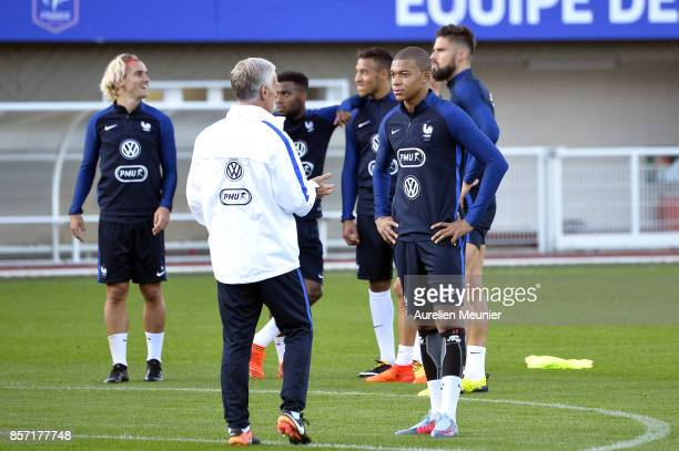 Kylian Mbappe of France speaks with France Head Coach Didier Deschamps during a France training session on October 3 2017 in Clairefontaine France