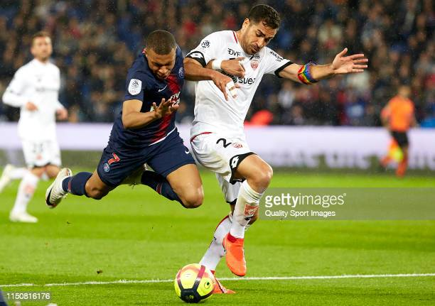 Kylian Mbappe of Paris SaintGermain competes for the ball with Wesley Lautoa of Dijon during the French Ligue 1 match between Paris SaintGermain and...