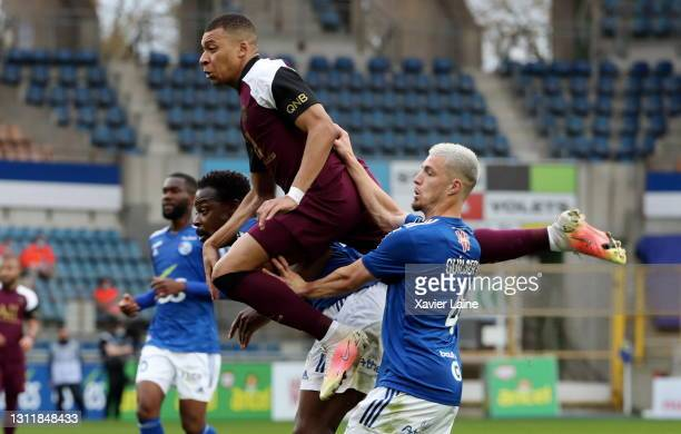 Kylian Mbappe of Paris Saint-Germain is catch by Lamine Kone and Frederic Guilbert of Strasbourg during the Ligue 1 match between Strasbourg and...