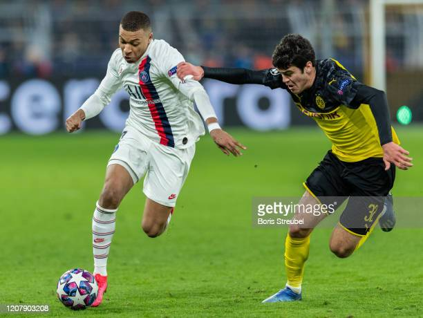 Kylian Mbappe of Paris SaintGermain is challenged by Giovanni Reyna of Borussia Dortmund during the UEFA Champions League round of 16 first leg match...