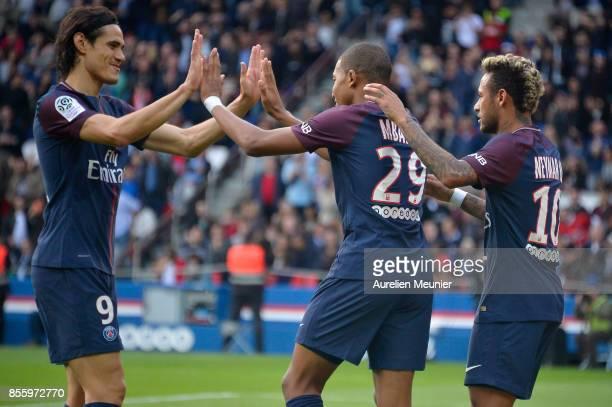 Kylian Mbappe of Paris SaintGermain is congratulated by teammates Edinson Cavani and Neymar Jr after scoring during the Ligue 1 match between Paris...