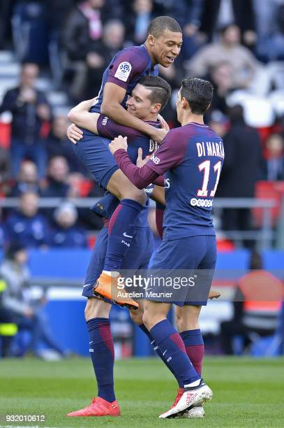 Kylian Mbappe of Paris SaintGermain is congratulated by teammates Julian Draxler and Angel Di Maria after scoring during the Ligue 1 match between...