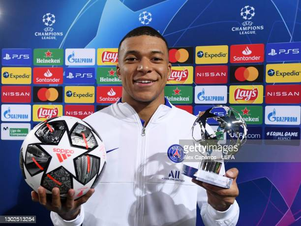 Kylian Mbappe of Paris Saint-Germain poses for a photo with the match ball and the player of the match award after the UEFA Champions League Round of...