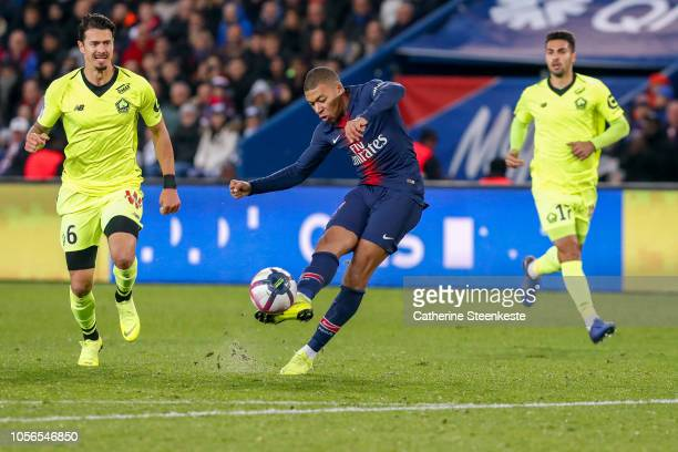 Kylian Mbappe of Paris Saint-Germain shoots the ball to score his first goal of the game against Jose Fonte and Rui Fonte of Losc during the Ligue 1...