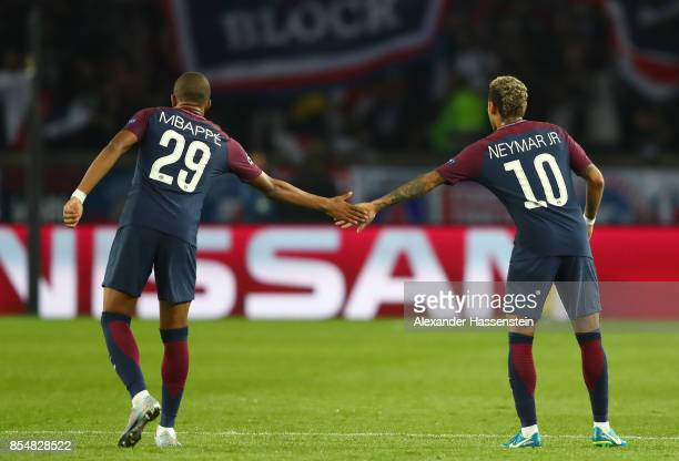 Kylian Mbappe of PSG and Neymar of PSG touch hands during the UEFA Champions League group B match between Paris SaintGermain and Bayern Muenchen at...