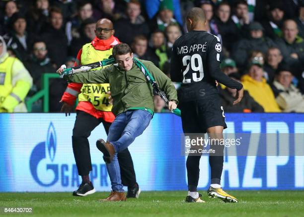 Kylian Mbappe of PSG avoids a streaker during the UEFA Champions League match between Celtic Glasgow and Paris Saint Germain at Celtic Park on...